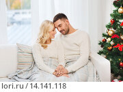 Купить «happy couple covered with plaid on sofa at home», фото № 14141118, снято 8 октября 2015 г. (c) Syda Productions / Фотобанк Лори