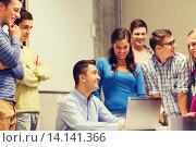 Купить «group of students and teacher with laptop», фото № 14141366, снято 7 сентября 2014 г. (c) Syda Productions / Фотобанк Лори