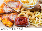 Купить «close up of fast food snacks on wooden table», фото № 14157262, снято 21 мая 2015 г. (c) Syda Productions / Фотобанк Лори