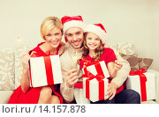 Купить «smiling family holding gift boxes and sparkles», фото № 14157878, снято 26 октября 2013 г. (c) Syda Productions / Фотобанк Лори