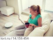 Купить «happy woman reading magazine with tea cup at home», фото № 14159454, снято 25 января 2015 г. (c) Syda Productions / Фотобанк Лори
