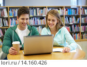 happy students with laptop in library. Стоковое фото, фотограф Syda Productions / Фотобанк Лори