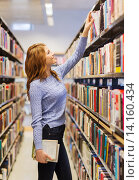 Купить «happy student girl or woman with book in library», фото № 14160434, снято 6 марта 2015 г. (c) Syda Productions / Фотобанк Лори
