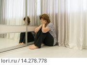 Купить «Woman with depression sitting in corner of the room», фото № 14278778, снято 6 ноября 2015 г. (c) Володина Ольга / Фотобанк Лори