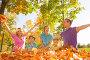 Счастливые родители с тремя детьми подбрасывают листья в осеннем парке, фото № 14338158, снято 26 сентября 2015 г. (c) Сергей Новиков / Фотобанк Лори