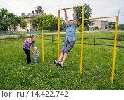 Папа показывает упражнения на турнике для своего сына. Молодые отец и мать с сыном на старом школьном стадионе в деревне. Стоковое фото, фотограф Алексей Маринченко / Фотобанк Лори