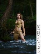 Дикая охотница-амазонка с копьем стоит в воде лесной реки. Стоковое фото, фотограф Pavel Reband / Фотобанк Лори