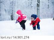 Купить «Маленький мальчик и девочка делают снеговика», фото № 14901274, снято 10 января 2015 г. (c) Ирина Мойсеева / Фотобанк Лори