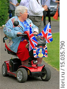 Купить «Senior female rides around in her scooter being patriotic at the Summer part in the park in Sherborne Dorset.», фото № 15035790, снято 7 июня 2012 г. (c) age Fotostock / Фотобанк Лори
