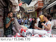 Turkish women making a bargain with a vendor (seller), street linking Grand and Spice Bazaars, Bazaar District, Istanbul, Turkey, Europe (2014 год). Редакционное фото, фотограф Eleanor Scriven / age Fotostock / Фотобанк Лори