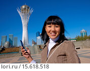 Купить «Ethnic Kazakh Girl With Cellphone In Front Of Baiterek Tower, Astana, Kazakhstan´», фото № 15618518, снято 20 сентября 2010 г. (c) age Fotostock / Фотобанк Лори