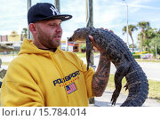 Купить «Man holding an alligator he has rescued from a local pond, Orlando, Florida.», фото № 15784014, снято 3 февраля 2015 г. (c) age Fotostock / Фотобанк Лори