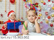 Купить «Девушка пишет письмо Санта-Клаусу, который сидит с подарком за ее спиной», фото № 15903002, снято 12 декабря 2015 г. (c) Иванов Алексей / Фотобанк Лори