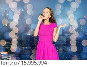 Купить «happy young woman with party horn over night city», фото № 15995994, снято 31 октября 2015 г. (c) Syda Productions / Фотобанк Лори