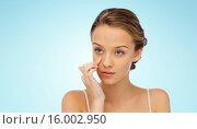 Купить «young woman applying cream to her face», фото № 16002950, снято 31 октября 2015 г. (c) Syda Productions / Фотобанк Лори