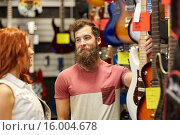 Купить «couple of musicians with guitar at music store», фото № 16004678, снято 11 декабря 2014 г. (c) Syda Productions / Фотобанк Лори