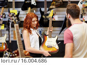 Купить «assistant showing customer guitar at music store», фото № 16004686, снято 11 декабря 2014 г. (c) Syda Productions / Фотобанк Лори