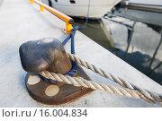 Купить «rusted iron mooring bollard with rope on pier», фото № 16004834, снято 20 сентября 2015 г. (c) Syda Productions / Фотобанк Лори