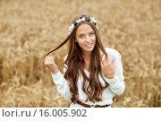 Купить «smiling young hippie woman on cereal field», фото № 16005902, снято 27 августа 2015 г. (c) Syda Productions / Фотобанк Лори