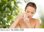 young woman squeezing pimple on her face. Стоковое фото, фотограф Syda Productions / Фотобанк Лори