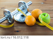 Купить «close up of dumbbell, fruits and measuring tape», фото № 16012118, снято 15 октября 2015 г. (c) Syda Productions / Фотобанк Лори