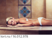 young woman lying on hammam table in turkish bath. Стоковое фото, фотограф Syda Productions / Фотобанк Лори