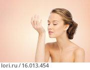 Купить «woman smelling perfume from wrist of her hand», фото № 16013454, снято 31 октября 2015 г. (c) Syda Productions / Фотобанк Лори