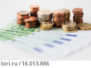 Купить «close up of euro paper money and coins on table», фото № 16013886, снято 30 июля 2015 г. (c) Syda Productions / Фотобанк Лори