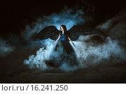 Купить «Девушка-ангел с черными крыльями на фоне дыма», фото № 16241250, снято 15 сентября 2015 г. (c) Евгения Литовченко / Фотобанк Лори