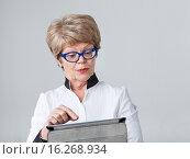 Купить «Пожилая женщина с удивлением смотрит на экран планшета и нажимает пальцем ссылку», фото № 16268934, снято 13 декабря 2015 г. (c) Кекяляйнен Андрей / Фотобанк Лори