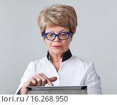 Купить «Сосредоточенная женщина пенсионер с улыбкой нажимает на тачскрин планшета», фото № 16268950, снято 13 декабря 2015 г. (c) Кекяляйнен Андрей / Фотобанк Лори