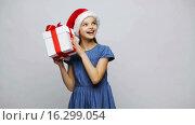 Купить «happy smiling girl in santa hat shaking gift box», видеоролик № 16299054, снято 12 декабря 2015 г. (c) Syda Productions / Фотобанк Лори