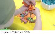 Купить «Ребенок украшает имбирное печенье глазурью», видеоролик № 16423126, снято 14 декабря 2015 г. (c) Алексндр Сидоренко / Фотобанк Лори