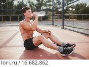 Спортивный мужчина сидит на уличной площадке и пьёт воду. Стоковое фото, фотограф Александр Сысоев / Фотобанк Лори