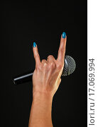 """Купить «Микрофон в женской руке, которая показывает жест """"коза"""" на черном фоне», фото № 17069994, снято 16 декабря 2015 г. (c) Anton Eine / Фотобанк Лори"""