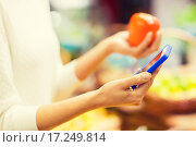 Купить «woman with smartphone and persimmon in market», фото № 17249814, снято 20 декабря 2014 г. (c) Syda Productions / Фотобанк Лори