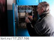 Купить «Пожилой мужчина снимает показания счетчика за электроэнергию в подъезде», эксклюзивное фото № 17257166, снято 24 декабря 2015 г. (c) Яна Королёва / Фотобанк Лори