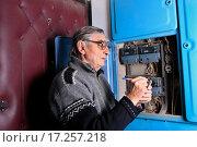 Купить «Пожилой мужчина снимает показания счетчика за электроэнергию в подъезде», эксклюзивное фото № 17257218, снято 24 декабря 2015 г. (c) Яна Королёва / Фотобанк Лори