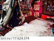 Женщина выделывает хлопок. Реконструкция традиционного таджикского домашнего уклада в центральном парке во время празднования праздника Навруза в городе Худжанд, Согдийская область, Таджикистан (2015 год). Редакционное фото, фотограф Николай Винокуров / Фотобанк Лори