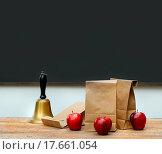 Купить «Lunch bags with apples and school bell on desk», фото № 17661054, снято 4 июня 2020 г. (c) easy Fotostock / Фотобанк Лори