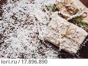 Купить «Подарки и искусственный снег на деревянном столе», фото № 17896890, снято 27 декабря 2015 г. (c) Инга Макеева / Фотобанк Лори