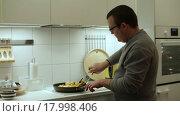 Купить «Мужчина жарит цыпленка на кухне», видеоролик № 17998406, снято 20 декабря 2015 г. (c) Валентин Беспалов / Фотобанк Лори