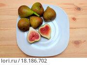 Ягоды инжира на белой тарелке, на деревянном столе. Стоковое фото, фотограф Irina Ugorova / Фотобанк Лори