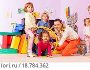Купить «Дети и учитель играют с обручами в классе детского сада», фото № 18784362, снято 28 ноября 2015 г. (c) Сергей Новиков / Фотобанк Лори