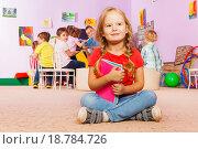 Купить «Портрет маленькой девочки, сидящей в обнимку с книгой на полу класса в детском саду», фото № 18784726, снято 28 ноября 2015 г. (c) Сергей Новиков / Фотобанк Лори