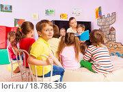 Купить «Дети слушают воспитателя, которая читает книгу», фото № 18786386, снято 28 ноября 2015 г. (c) Сергей Новиков / Фотобанк Лори