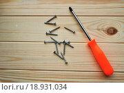 Купить «Крестовая отвертка и шурупы на деревянной поверхности», фото № 18931034, снято 19 июля 2018 г. (c) Зезелина Марина / Фотобанк Лори