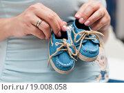 Купить «Девушка держит в руках детские ботиночки», эксклюзивное фото № 19008058, снято 1 ноября 2015 г. (c) Игорь Низов / Фотобанк Лори