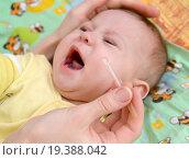 Женщина закапывает капли в нос больному плачущему младенцу. Лечение. Стоковое фото, фотограф Ирина Борсученко / Фотобанк Лори