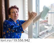 Купить «Пожилая женщина моет окно», эксклюзивное фото № 19556942, снято 24 декабря 2015 г. (c) Вячеслав Палес / Фотобанк Лори